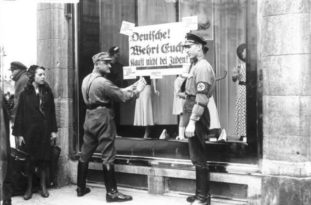 "Petugas di luar toko Yahudi di Berlin menempelkan poster bertuliskan ""Jerman! Pertahankan dirimu! Jangan membeli dari orang-orang Yahudi!"" (""Deutsche! Wehrt Euch! Kauft nicht bei Juden!"")."