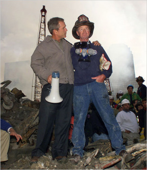 George Bush at ground zero – As rescue efforts continue in the rubble of the World Trade Center, President Bush puts his arms around firefighter Bob Beck while standing in front of the World Trade Center debris during a tour of the devastation, Friday September 14, 2001. Bush is standing on a burned fire truck. Mayor Rudolph Giuliani said 4,763 people have been reported missing in the devastation of the World Trade Center. (Doug Mills/The Associated Press)